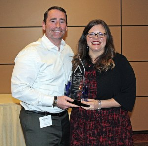 Nicole Hajdrowski, VP of training and development for West Corp. Unified Communication Services, accepts the 2016 Chicagoland Learning Leader of the Year Award from Caveo Learning CEO Jeff Carpenter
